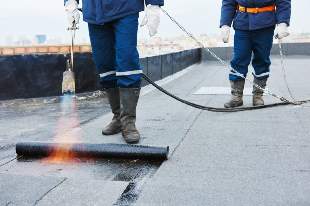 Flat roof installation. Heating and melting bitumen roofing felt by flame torch at construction site